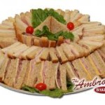 A Tray Of Convenient Made Fresh Sandwiches Ham Roast Beef And Turkey Are Paired With Cheeses White Wheat Bread Garnished Cherry Tomatoes